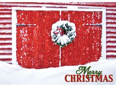 close up red barn doors with snow and wreath